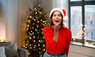 woman in santa hat sending air kiss on christmas