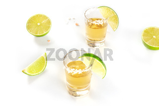 Golden tequila with lime and salt, shot glasses on a white background