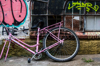 Worn pink bike without wheel on a frayed wall.