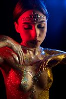 Beautiful girl in gold glitter and bodyart shot