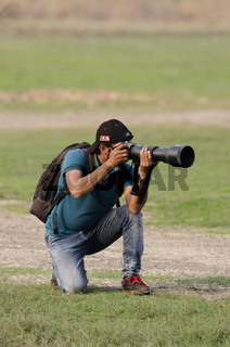 Wildlife photographer outdoor, sitting and taking photos