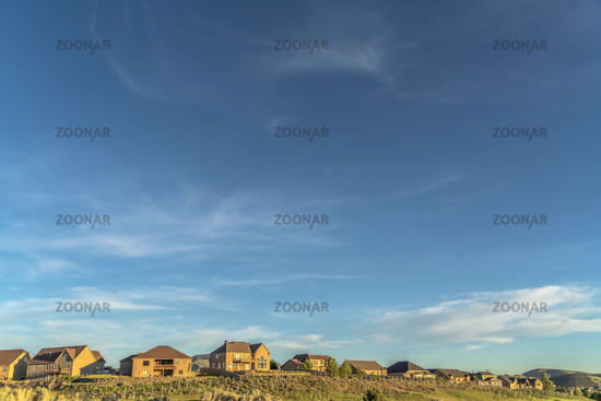 Blue sky and clouds over houses and grass covered hill viewed on a sunny day
