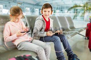 Geschwister Kinder spielen mit Tablet und Smartphone