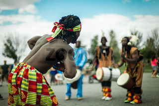 African guy dancing with blurry djembe players in the background