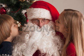 Children whispering to Santa Claus