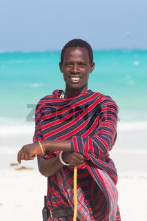 Traditonaly dressed maasai black man on picture perfect tropical Paje beach, Zanzibar, Tanzania, East Africa.