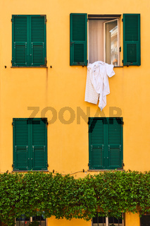 Wall of house with windows with shutters