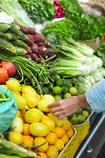 Woman choosing fruit at vegetable market