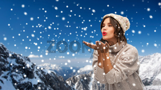 young woman in knitted winter hat sending air kiss