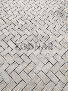 Rectangular cement block floor in zigzag pattern.