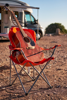 Vertical view red acoustic guitar on a folding chair near recreational vehicle motor home trailer