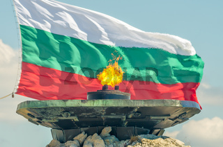 Eternal fire burns against the backdrop of the National Flag of Bulgaria. The Shipka Freedom Monument, Gabrovo, Bulgaria. Dedicated to the Battle of Shipka Peak (August 1877)