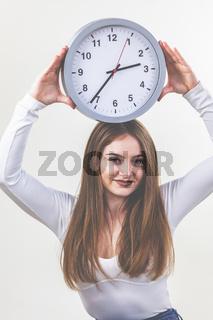 Frau, weißes Shirt und Jeans, brünette, lange Haare, hält eine Uhr in den Händen.