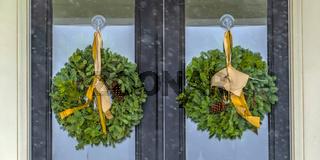 Welcoming wreaths hanging on a glass door in Utah