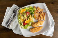 Flat lay of salad with french fries and chicken tenders arranged on plate