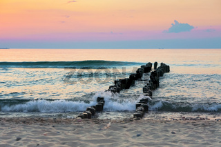 sunset on the seashore, breakwaters in the sea at sunrise
