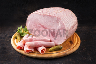 Traditional German boiled ham as piece and sliced decorated with gherkin and parsley as top view on a wooden board with copy space