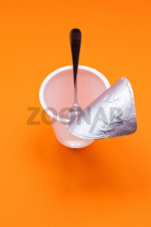 empty clean yogurt cup with spoon on an orange background