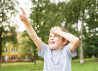 Boy 5 years old looks up at something and shows finger in summer park on background of trees
