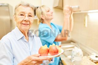 Alte Frau mit einem Teller Obst in der Küche