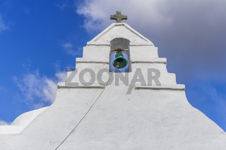 Bell tower at a Greek island against blue sky background.
