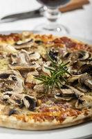 Nahaufnahme von Pilzpizza mit Rosmarin