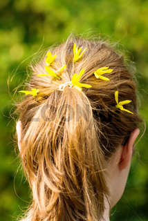Young woman with plait and yellow flowers in hair