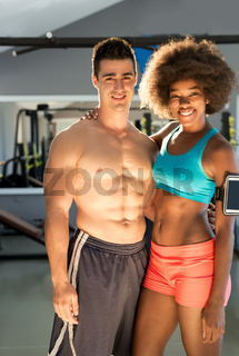 Athletic man and  afro american woman posing in gym