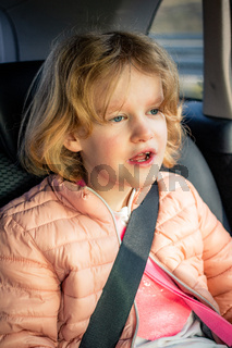 Child sits strapped in the car