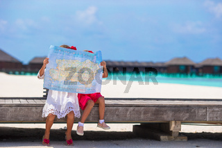 Adorable little girls with map of island on beach