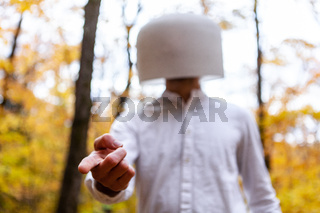 Man in white has a crystal bowl on his head while pointing straight