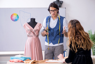 Young male tailor teaching female student