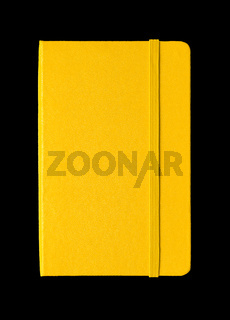 Yellow closed notebook isolated on black