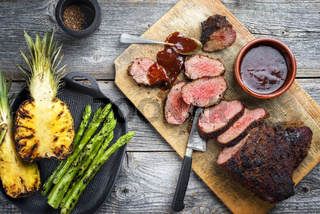Barbecue dry aged wagyu tri tip steak with grilled pineapples and green asparagus top view on a wooden cutting board