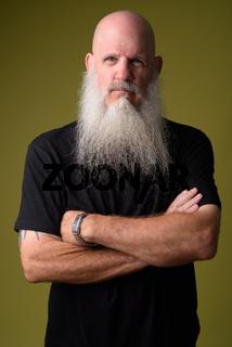 Serious mature bald man with long gray beard crossing arms