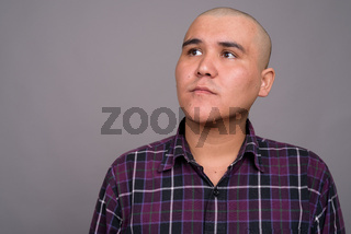 Young bald Asian businessman against gray background