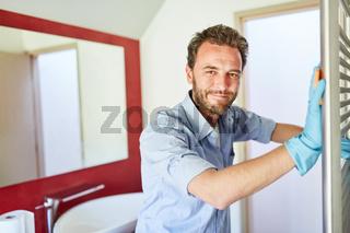 Hausmann beim staubwischen am Heizkörper