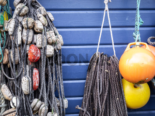 Fishing nets and ropes hang outside on the house wall