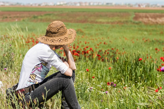 Woman with hat sitting in a meadow full of flowers, enjoying the nature
