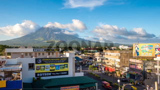 LEGAZPI, PHILIPPINES - JANUARY 5, 2018: - Mount Mayon volcano looms over the city as daily life goes on.
