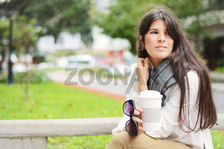 Woman holding paper coffee cup in the street.