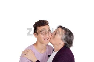 Grandmother kissing her teen grandson
