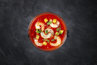 Coctel de gambas, Mexican shrimp cocktail with avocado, shot from the top on a dark background