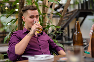 Man sitting outdoors and drinking beer from glass