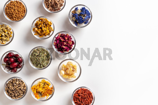 Dried herbs in bowls on a white background with copy space, top view