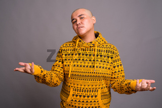 Young bald Asian man against gray background