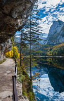 Autumn alpine view. Peaceful mountain lake with clear transparent water and reflections and ferrata stairs. Gosauseen or Vorderer Gosausee lake, Upper Austria. Dachstein summit and glacier in far.