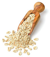 raw oatmeal in the wooden scoop, isolated on white