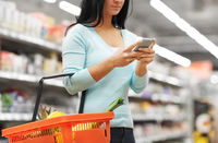 woman with smartphone buying food at supermarket