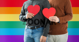 close up of happy male couple holding red hearts